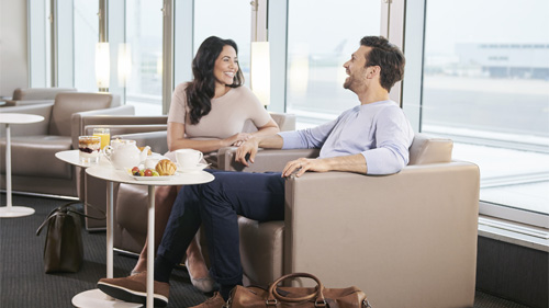 A man and a woman drinking in the lounge