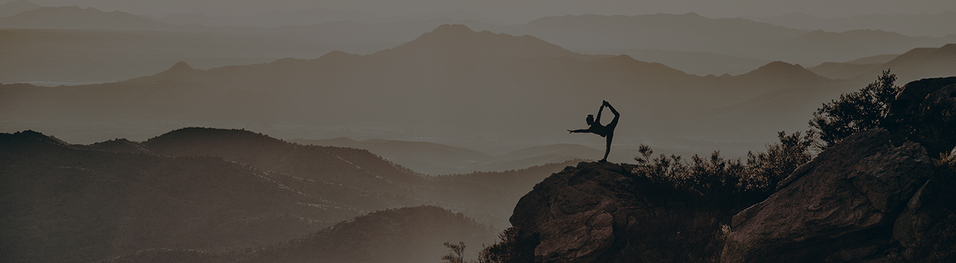 A ballet dancer stretching surrounded by mountains