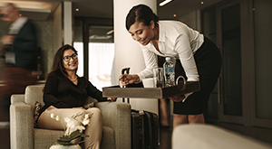 A woman serves drinks to a traveler in the airport lounge