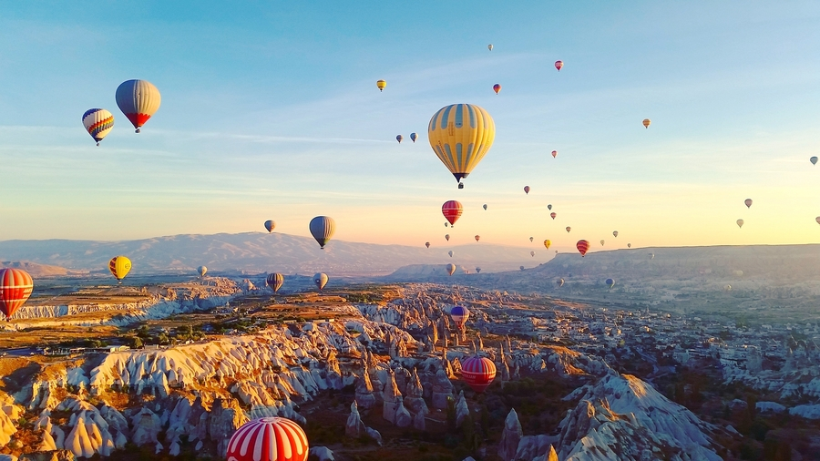 Hot air balloons flying over the volcanic peaks and rocky valleys in Cappadocia, Turkey