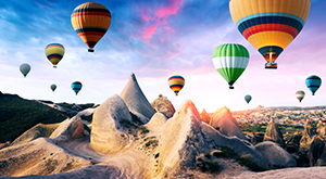 Colorful hot air balloons flying over the volcanic peaks of Göreme National Park in Cappadocia, Anatolia – the heartland of Turkey